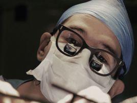 Kamera koncentruje się na twarzach lekarzy (kadr z filmu)