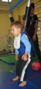 Dziecko ćwiczy w specjalnej uprzęży  zamocowanej do szyny podsufitowej. (fot. TVP)